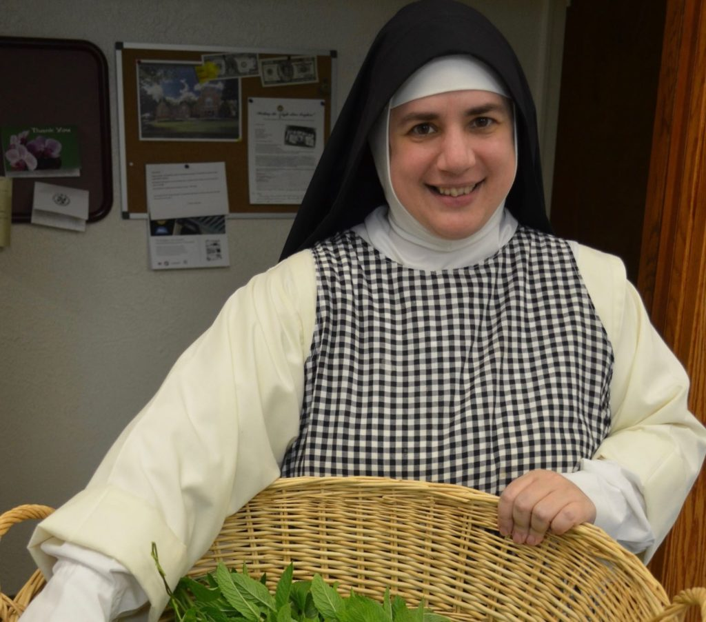 A nun is holding a basket and smiling at the camera