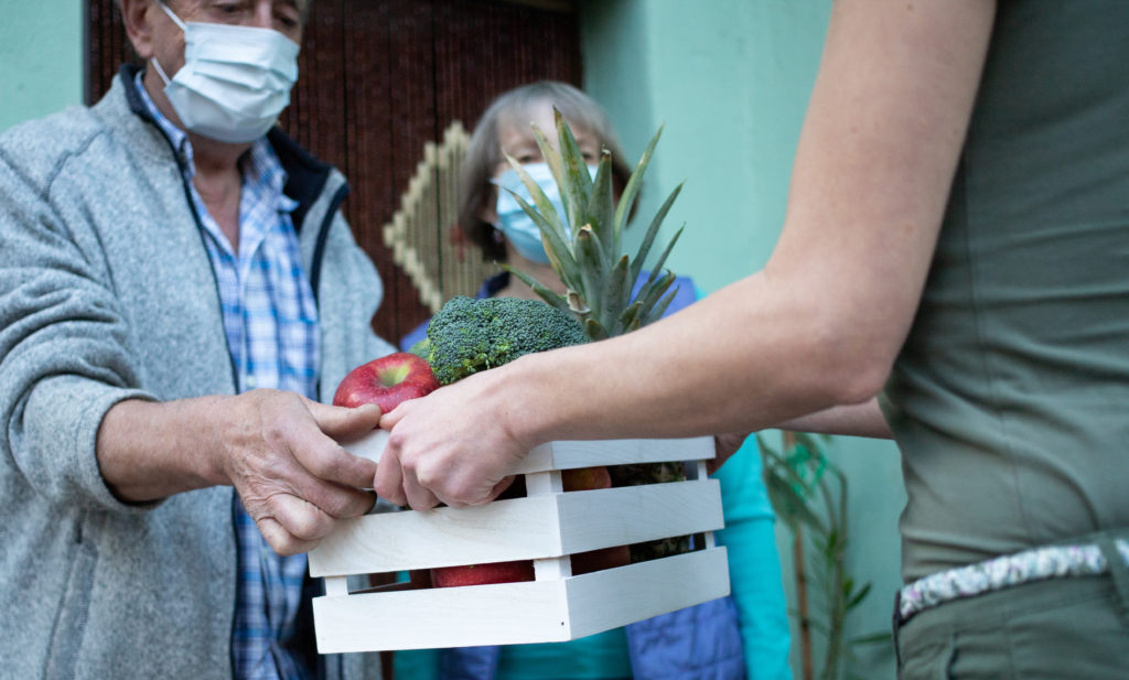 An older couple wearing PPE masks receive the gift of a box of fruit and vegetables from a visitor