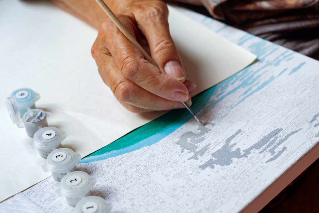 An older person is using a painting by numbers kit