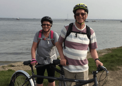 A man and a lady pose beside their bicycles