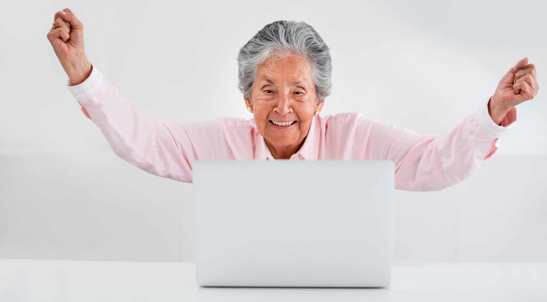 An elderly lady celebrates doing something on her laptop