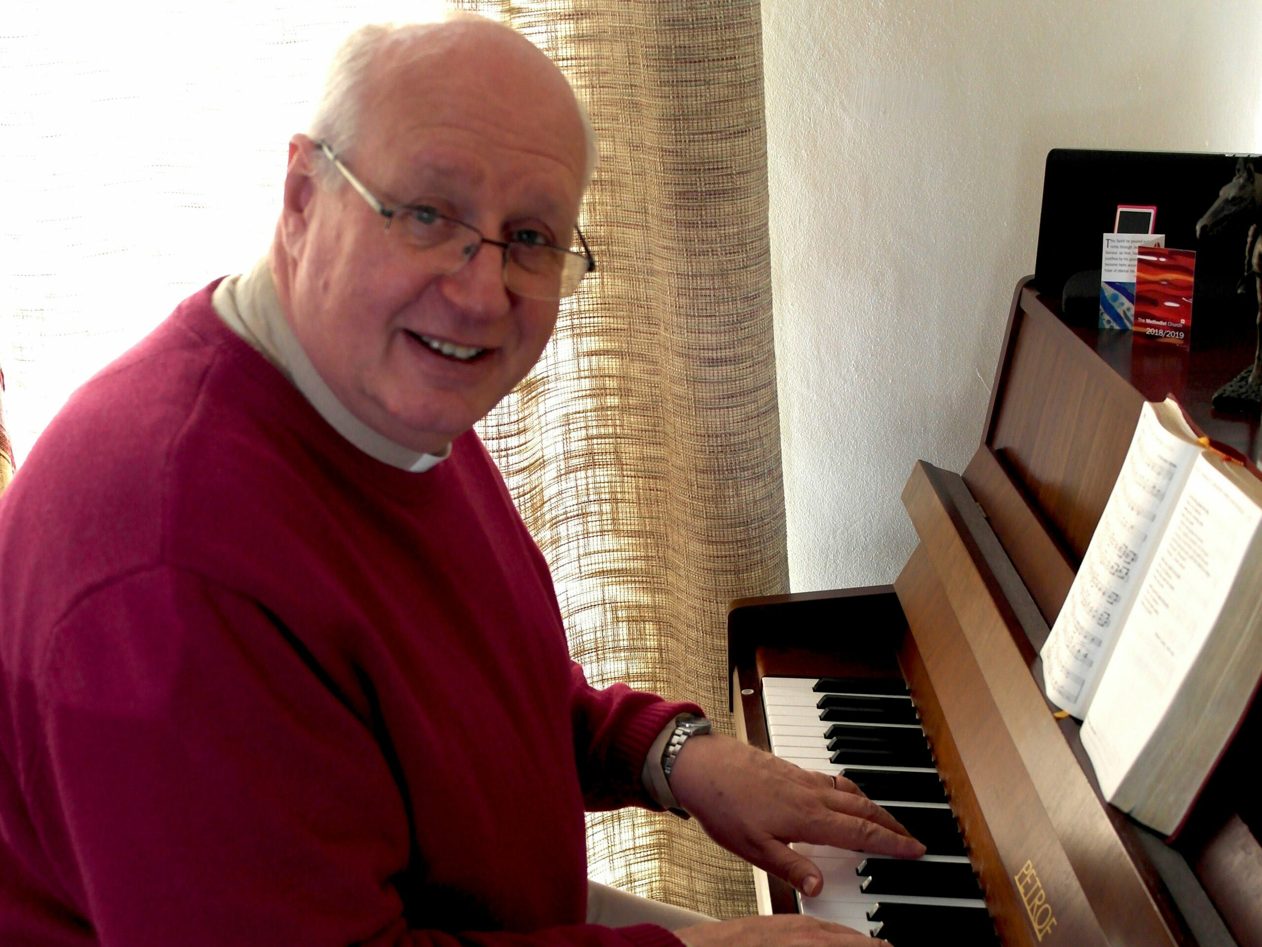 Reverend Richard Teal is playing the piano at home