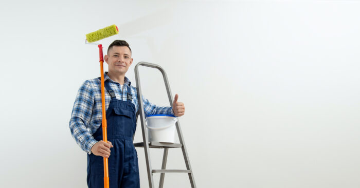 Young man in dungarees with stepladders and a paint roller