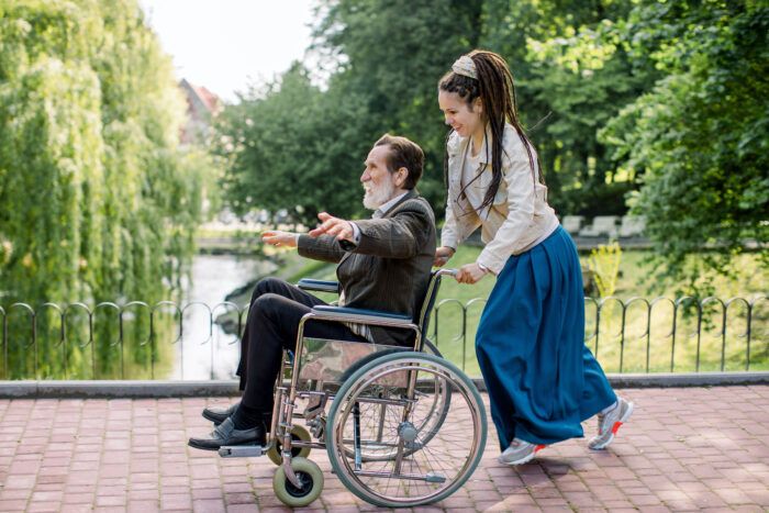 young adult with dreadlocks and trainers is smiling, while pushing an older person in a wheelchair, across a bridge